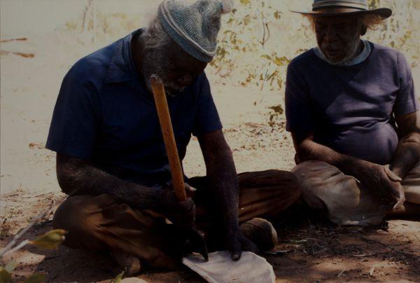 Two men making bark utensils